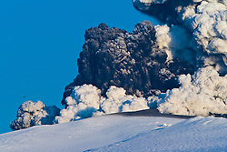 A lone helicopter can be seen above the left cloud at the cloud of ash from the Eyjafjallajoekull erupting volcano in Iceland. .©2010 Michael Schofield. All Rights Reserved.