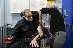 © Licensed to London News Pictures. 01/05/2021. London, UK. A NHS Covid-19 vaccinator administers the Oxford/AstraZeneca vaccine to a man at a vaccination centre in Haringey, north London. In the UK, over 34.2 million people have received a first dose and almost 14.5 million are fully vaccinated. People aged 40and over can now book their appointments through the national booking website as part of the next phase of the government's vaccination programme. <br /> <br /> ***Permission Granted*** <br /> <br /> Photo credit: Dinendra Haria/LNP