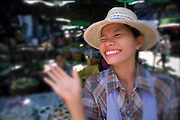 A woman from Thailand waves at the camera with a big smile on her face.