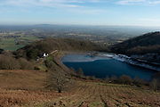 Landscape view across a frozen reservoir from the top of the Malvern Hills in Great Malvern, United Kingdom. The Malvern Hills are a range of hills in the English countryside of Worcestershire, Herefordshire and Gloucestershire.