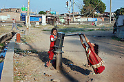Two girls are playing on one of the hazardous, and now sealed, hand-pumps in Arif Nagar, one of the water-affected colonies standing next to the abandoned Union Carbide (now DOW Chemical) industrial complex, site of the infamous 1984 gas tragedy in Bhopal, Madhya Pradesh, central India.