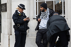 London, UK. 11 October, 2019. Police officers carry out a stop and search on a man of colour from charity Who Is Hussain? attending an Extinction Rebellion protest outside the main entrance to the BBC's New Broadcasting House on the fifth day of International Rebellion protests.