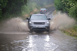 © Licensed to London News Pictures 17/06/2021. Crockenhill, UK. Flood water spray from cars. Torrential rain is causing roads to flood in Crockenhill, Kent. Photo credit:Grant Falvey/LNP