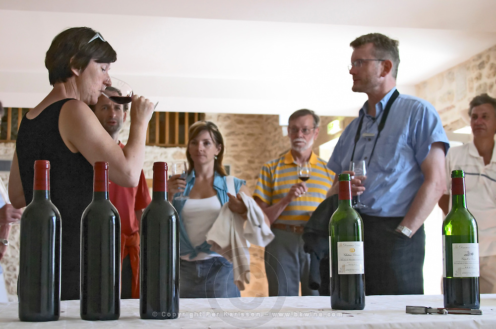 Visiting wine enthusiasts tasting the wine in the wine tasting room, bottles in the foreground and people holding glasses Chateau Potensac Cru Bourgeois Ordonnac Medoc Bordeaux Gironde Aquitaine France