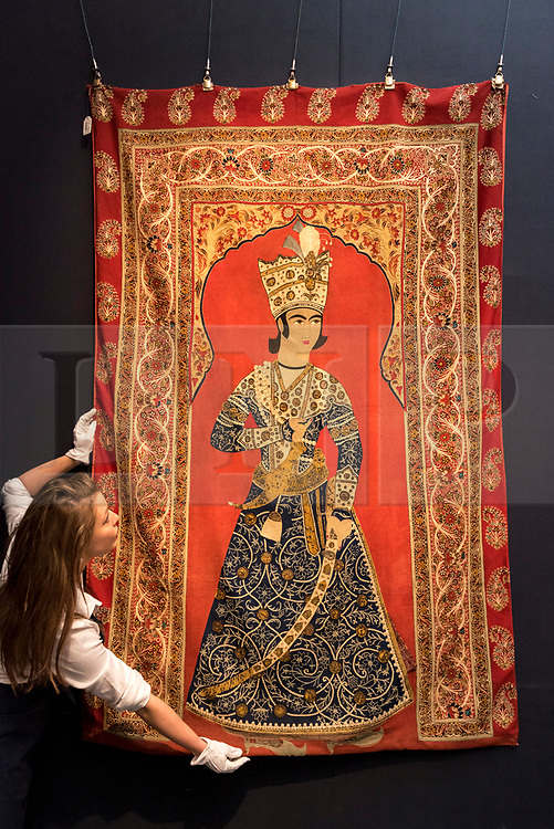 """© Licensed to London News Pictures. 20/04/2018. LONDON, UK. A technician presents """"A Qajar Rasht embroidered panel depicting a prince, Persia"""", 19th century, (Est. GBP8-12k) at a preview of works in Sotheby's 20th Century Middle East, Orientalist and Islamic upcoming art sales in New Bond Street.  The works will be sold at auction in the last week of April.    Photo credit: Stephen Chung/LNP"""