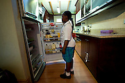 Masindi (9 years old) look in the fridge for something to eat after at school.