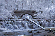 Snow Covered Trees Framing A Stone Bridge And Waterfall During Winter In The Park, Sharon Woods, Southwestern Ohio, USA