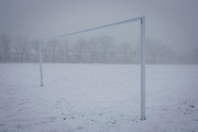 Cancelled football pitch and empty landscape of snowbound goal posts in wintry public park in south London. During a prolonged cold spell of bad weather, snow fell continuously on the capital on Sunday, allowing families the chance to enjoy the bleak conditions, here in Ruskin Park in the borough of Lambeth.