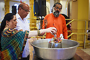 10 AUGUST 2012 - PHOENIX, AZ: A Hindu priest helps a couple make an offering to a diety during the celebration of Janmashtami at Ekta Mandir, a Hindu temple in central Phoenix. Janmashtami is the Hindu holy day that celebrates the birth of Lord Krishna. Hindu communities around the world celebrate the holy day. In Arizona, most of the Hindu temples in the Phoenix area have special celebrations of the day.   .PHOTO BY JACK KURTZ