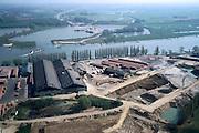 Nederland, Gelderland, Angeren, 04-04-2002; steenfabriek aan de Neder-Rijn (Pannerdensch Kanaal), uit de kleiputten rond de fabriek wordt  klei gebaggerd om in de ovens van de fabriek tot  baksteen en dakpannen verwerkt te worden; aan de overzijde van de rivier het natuurgebied Kandia met de aanleg van de Betuweroute, naar de horizon; strekdammen, uiterwaarden, bouwen .Deel van een serie over Betuweroute / infrastructuur.<br /> luchtfoto (toeslag), aerial photo (additional fee)<br /> photo/foto Siebe Swart