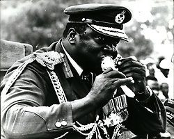 Jan. 01, 1978 - Big bite by big daddy: During the celebrations of the 7th Anniversary of his Military Coup. Life President Idi Amin, YC,DSo,MC, conqueror of the British Empire and Commander-in-Chief of the armed forces takes a large bite at a roasted chicken while watching the parade at Koboko Uganda. (Credit Image: © Keystone Press Agency/Keystone USA via ZUMAPRESS.com)