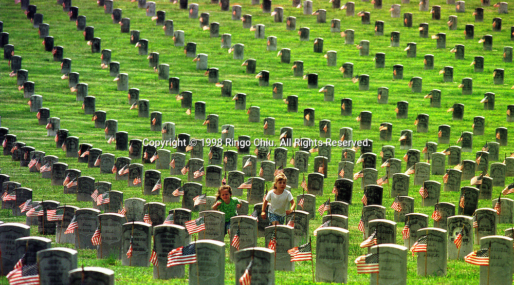 Kellie Mcdougle (left) and Katellyn Mcdougle run across the graves after the scouts placed flags on them. Hundreds Americans attended the Memorial Day Ceremony at Los Angeles National Cemetery in West Los Angeles, California, USA. (Photo by Ringo Chiu/PHOTOFORMULA.com).