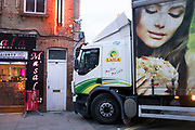HGV lorry struggling to turn onto Brick Lane gets stuck and cannot move. The large scale advertising on the side of this vehicle adds a strange dimension as the woman depicted looks on hungrily at her food, while the lorry is headed on a collision course with an Indian restaurant. London, UK.