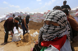 April 27, 2018 - Bureij, Gaza Strip - Palestinian demonstrators fill bags with sand to create barricades to protect themselves during clashes with Israeli security forces during tents protest demanding the right to return to their homeland, in Bureij in the cetner of Gaza strip on April 27, 2018  (Credit Image: © Yasser Qudih/APA Images via ZUMA Wire)