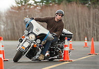 Laconia Patrolman Robb Sedgley works his way around the cones of the Police Motorcycle Course at Laconia Airport Wednesday morning.  (Karen Bobotas/for the Laconia Daily Sun)