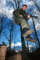 A member of the Parachute Regiment lunges through an assault course in Aldershot military training area, he is equipped with a LSW (light support weapon), designed to give covering fire to a section/platoon. Photograph by Terry Fincher