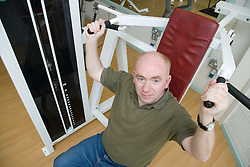 Man using shoulder press at the gym to strengthen upper body,