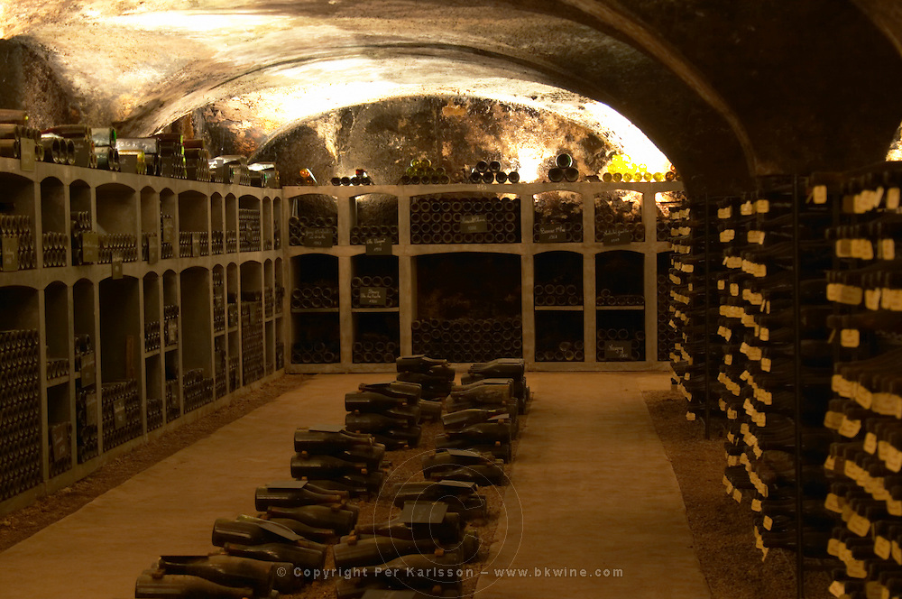 In the underground wine cellar: piles of thousands of bottles in the treasure chamber where the oldest bottles are kept Burgundy wine on a gravelly pebbly soil vaulted vault ceiling with contrasting lights, Maison Louis Jadot, Beaune Côte Cote d Or Bourgogne Burgundy Burgundian France French Europe European