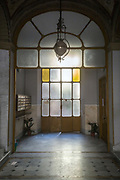 Light streams through a stained glass window in the lobby of an Art Nouveau apartment building in Genoa, Italy.