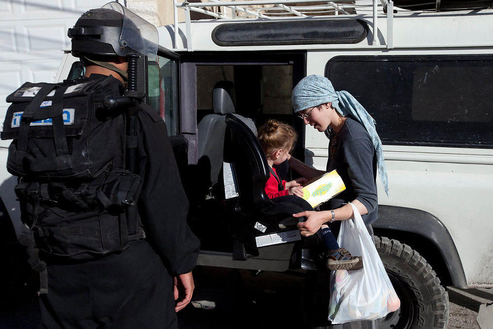 An Israeli policeman stands guard as a Jewish woman and her child exit an armored vehicle at the entrance to Beit Yonatan in the east Jerusalem neighborhood of Silwan, prior to a visit by Israeli parliament members of the National Union party to the building that houses several Jewish families in the mostly Palestinian area on December 27, 2010.