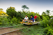 29 JUNE 2013 - BATTAMBANG, CAMBODIA:  Bamboo Train carrying Cambodian passengers to O Sra Lav, a small village southeast of Battambang. The bamboo train, called a norry (nori) in Khmer is a 3m-long wood frame, covered lengthwise with slats made of ultra-light bamboo, that rests on two barbell-like bogies, the aft one connected by fan belts to a 6HP gasoline engine. The train runs on tracks originally laid by the French when Cambodia was a French colony. Years of war and neglect have made the tracks unsafe for regular trains.  Cambodians put 10 or 15 people on each one or up to three tonnes of rice and supplies. They cruise at about 15km/h. The Bamboo Train is very popular with tourists and now most of the trains around Battambang will only take tourists, who will pay a lot more than Cambodians can, to ride the train.       PHOTO BY JACK KURTZ