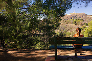 I hiker stops to enjoy the view of the Hollywood sign from the Mt. Hollywood Trail in Griffith Park, Los Angeles, California.  (model released)