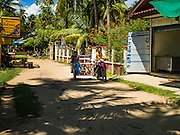 18 JUNE 2016 - DON KHONE, CHAMPASAK, LAOS:  A Lao family in a tuk-tuk (three wheeled taxi) in Don Khone. Don Khone Island, one of the larger islands in the 4,000 Islands chain on the Mekong River in southern Laos. The island has become a backpacker hot spot, there are lots of guest houses and small restaurants on the north end of the island.    PHOTO BY JACK KURTZ