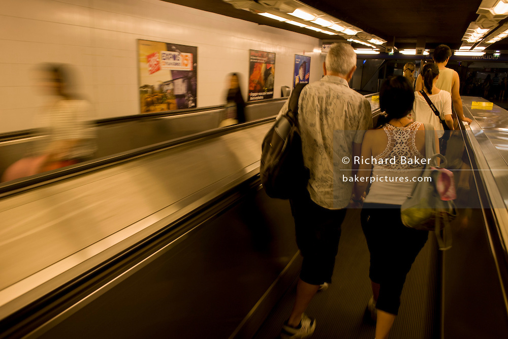 Blurring passengers travel on a moving escalator underground in the Paris Metro.
