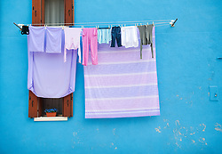 Washing hanging from colourful houses in village of Burano near Venice in Italy