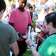 "YARMOUTH, Maine- 8/13/17 -- Tommy Ishimwe, 15, of Yarmouth, center, helps light candles for marchers as part of a meeting, demonstration and march in solidarity against violence and rioting in Charlottesville, Va.   About 40 people gathered and marched together singing ""We Shall Overcome"" on Sunday evening to demonstrate solidarity with the victims of weekend violence in Charlottesville, Va which killed three and injured dozens. Photo by Roger S. Duncan for The Forecaster."