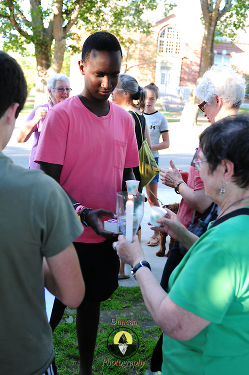 """YARMOUTH, Maine- 8/13/17 -- Tommy Ishimwe, 15, of Yarmouth, center, helps light candles for marchers as part of a meeting, demonstration and march in solidarity against violence and rioting in Charlottesville, Va.   About 40 people gathered and marched together singing """"We Shall Overcome"""" on Sunday evening to demonstrate solidarity with the victims of weekend violence in Charlottesville, Va which killed three and injured dozens. Photo by Roger S. Duncan for The Forecaster."""