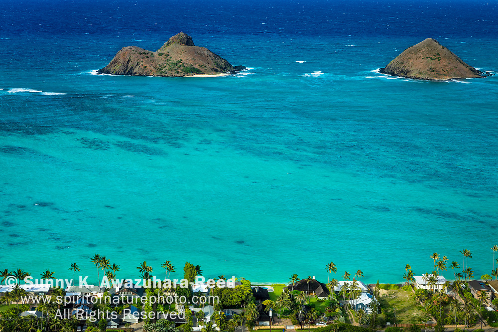 Aerial view of Mokulua Islands, turquoise ocean, and Lanikai neighborhood. Kailua, Island of Oahu, Hawaii.