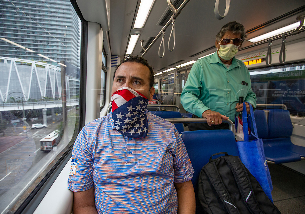 Metrorail passenger Gregorio Moya, 51, wears an American flag scarf to protect himself from COVID19 in Miami on Wednesday, April 1, 2020.