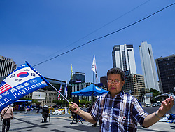 June 16, 2018 - Seoul, Gyeonggi, South Korea - A Korean evangelical Christian prays before a protest against South Korean President Moon Jae-in. He said he supports jailed former President Park Geun-hye. Moon was elected in 2017 after Park was impeached, tried and convicted on corruption charges. The protesters allege that Moon is too soft on North Korea and can't be trusted to negotiate with North Korean leader Kim Jong-un. They support US President Donald Trump's efforts to negotiate with the North Korean strongman. (Credit Image: © Jack Kurtz via ZUMA Wire)