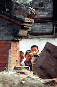 Chinese children play amongst the rubble of a courtyard house that was recently demolished in their Hutong neighborhood in the Chongwenmen area of central Beijing. Hutongs, maze-like gray-walled residential areas that have defined Beijing since the beginning of the Yuan Dynasty nearly 800 years ago are being systematically destroyed in an effort to spruce up Beijing before the Olympics in 2008.