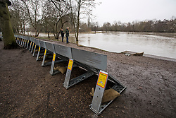 © Licensed to London News Pictures. 01/02/2021. Weybridge, UK. Member son the public walk past flood defences installed along the river Thames at Weybridge in Surrey. Extra precautionis being taken because In 2014 Weybridge and the surrounding area was badly hit by flooding. Photo credit: Ben Cawthra/LNP