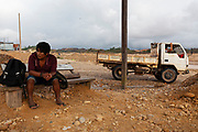 A young man waits for transportation to go to work at a gold mining camp in Huepetuhe, Peru. Huepetuhe is a town where the largest gold extraction is concentrated within the mining corridor in the Peruvian Amazon.