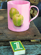 Weathered pink plastic cup beside a box of matches on an old wooden table, Sulawesi, Indonesia, Southeast Asia