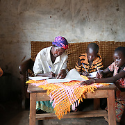 CAPTION: Since starting adult education, Florence has enjoyed studying alongside her children at home. Sometimes she is even able to assist them with their homework. LOCATION: Apapai Parish, Otuboi Sub-county, Kalaki County, Kaberamaido District, Uganda. INDIVIDUAL(S) PHOTOGRAPHED: From left to right: Florence Agabo, Francis Eyunu and Sarah Amwodo.