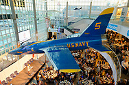 Garden City, New York, U.S. June 6, 2019. On stage, speaker talking about role of Grumman employees in Apollo mission is seen from third level of atrium of Cradle of Aviation Museum, during Apollo at 50 Anniversary Dinner, an Apollo astronaut tribute celebrating the Apollo 11 mission Moon landing. U.S. Navy Blue Angels Grumman F-11A Tiger jet is suspended from ceiling.