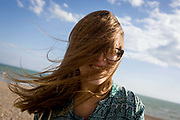A 19 year-old girl's hair blows across her face at the beach at Brighton, England. Wearing glasses to rectify her short-sightedness (myopia) the young lady can see little as her long hair sweeps over her eyes. It is a sunny day on the southern English coastal town, with a shingle beach stretching down to the sea.