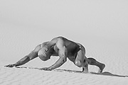 naked muscular man in sand