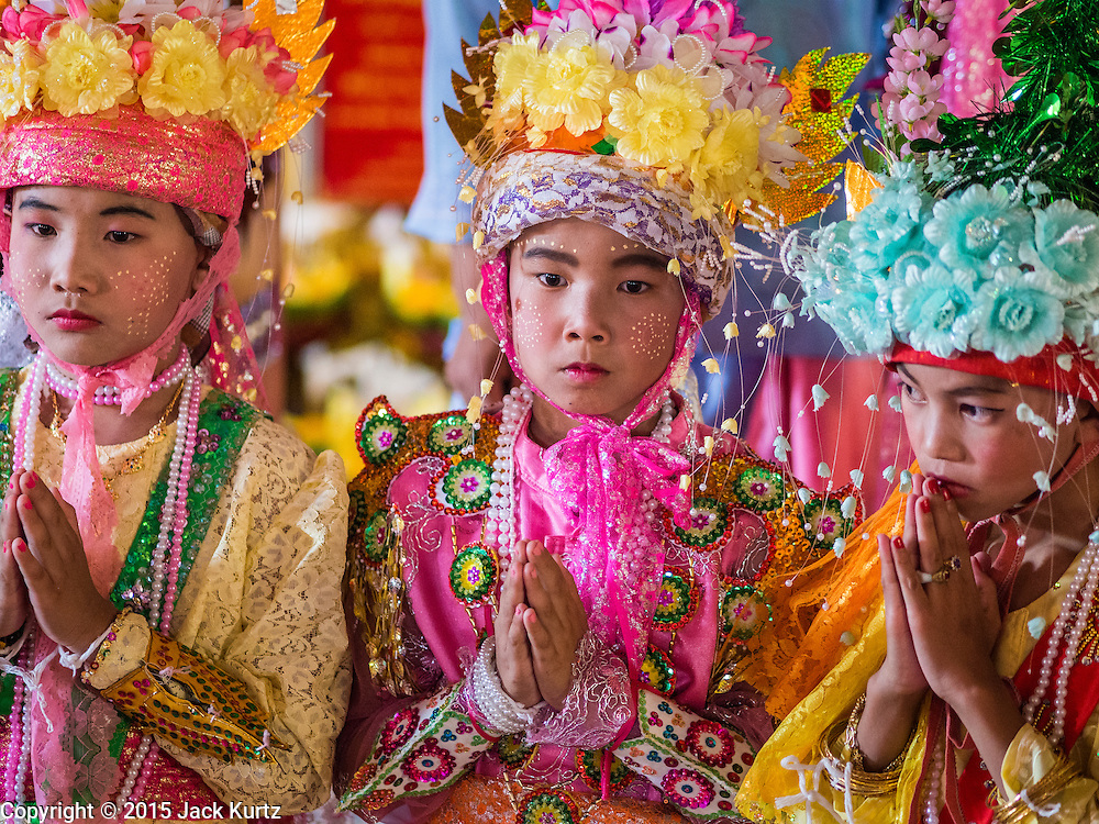 """04 APRIL 2015 - CHIANG MAI, CHIANG MAI, THAILAND:  Boys being ordained as a Buddhist novices pray at Wat Phra Singh during the Poi Song Long Festival in Chiang Mai. The Poi Sang Long Festival (also called Poy Sang Long) is an ordination ceremony for Tai (also and commonly called Shan, though they prefer Tai) boys in the Shan State of Myanmar (Burma) and in Shan communities in western Thailand. Most Tai boys go into the monastery as novice monks at some point between the ages of seven and fourteen. This year seven boys were ordained at the Poi Sang Long ceremony at Wat Pa Pao in Chiang Mai. Poy Song Long is Tai (Shan) for """"Festival of the Jewel (or Crystal) Sons.     PHOTO BY JACK KURTZ"""