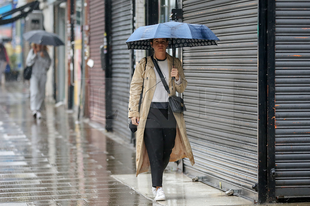 © Licensed to London News Pictures. 14/09/2021. London, UK. A woman shelters under an umbrella during rainfall in north London. A yellow weather warning for heavy rain is in place in London and parts of South East England. Photo credit: Dinendra Haria/LNP