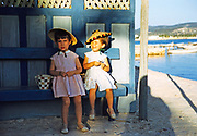 Two pretty little girls sitting on beck by the sea, island of Ibiza, Balearic Islands, Spain,  1950s