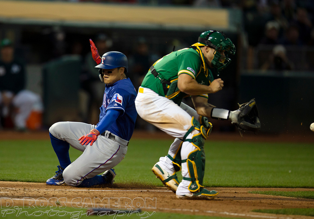 Jul 25, 2019; Oakland, CA, USA; Texas Rangers Shin-Soo Choo slides home safely on a single by Texas Rangers shortstop Elvis Andrus during the fifth inning of a baseball game as Oakland Athletics catcher Josh Phegley (19) waits for the late relay  at Oakland Coliseum. Mandatory Credit: D. Ross Cameron-USA TODAY Sports
