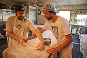 Jamestown, RI - 7 May 2007. Andrea Colognese, baker and co-owner of The Village Hearth Bakery and Cafe, shaping baguettes with his assistance.