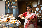 A woman helps herself to the buffet at the Park Hotel, New Delhi, India
