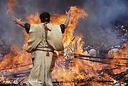 A Yamabushi (Mountain Priest) throws votive tablets onto a large bonfire of ceder branches which he will later walk across in the Hi Watari, fire walking, festival of Takao san Guchi near Tokyo, Japan. Sunday March 11th 2007