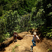 Hikers explore the Kalalau Trail, one of Hawaii's most famous hikes on the North Shore of Kauai in Hawaii. The trail runs 11 miles along the Na Pali coast and provides amazing views.